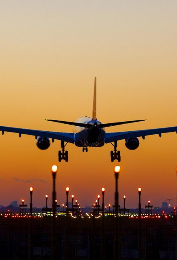 Commercial aircraft landing with sunset