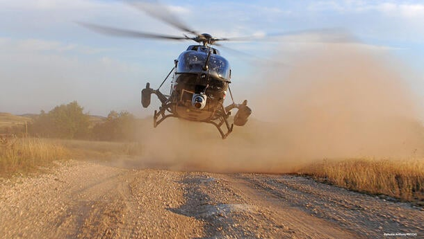 Airbus H145M landing on a dirt road with bellows of dust around it.