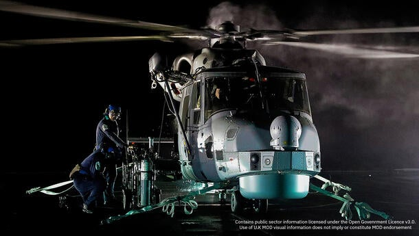 Leonardo AW159 Helicopter on a U.K. Royal Navy Ship at night with a spotlight on it